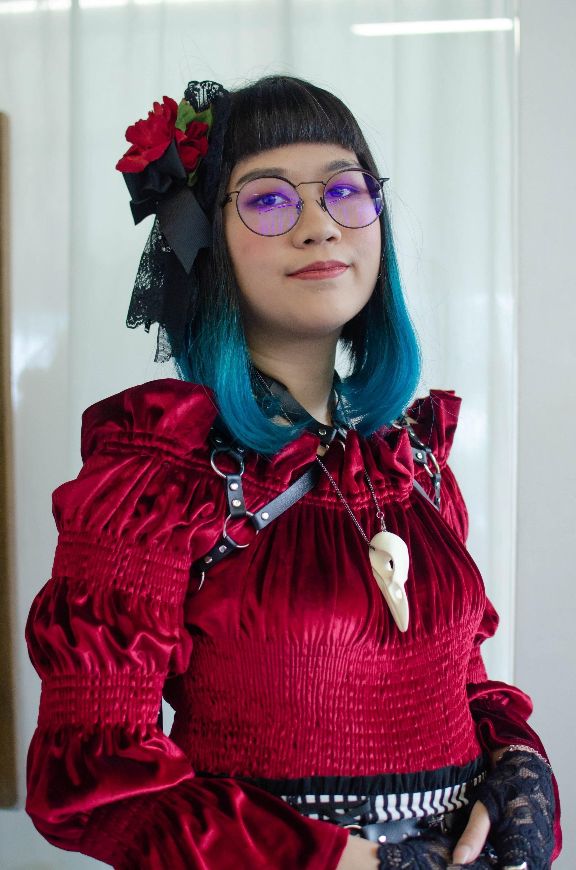 Asian woman in a red doll costume with dip dyed blue hair