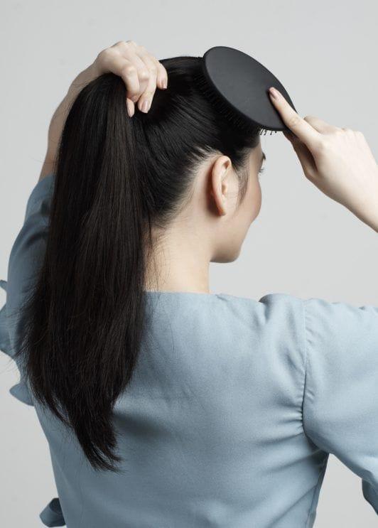 Braid ponytail: Asian woman putting hair in high ponytail
