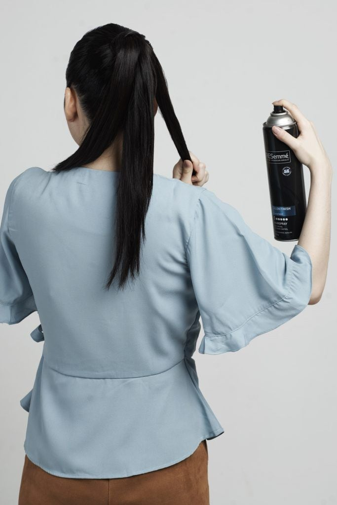Braid ponytail: Asian woman spritzing hairspray