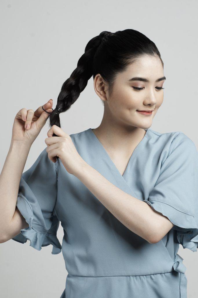 Braid ponytail. Asian woman braiding her hair