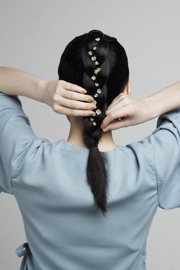 Asian woman embellishing her braid ponytail