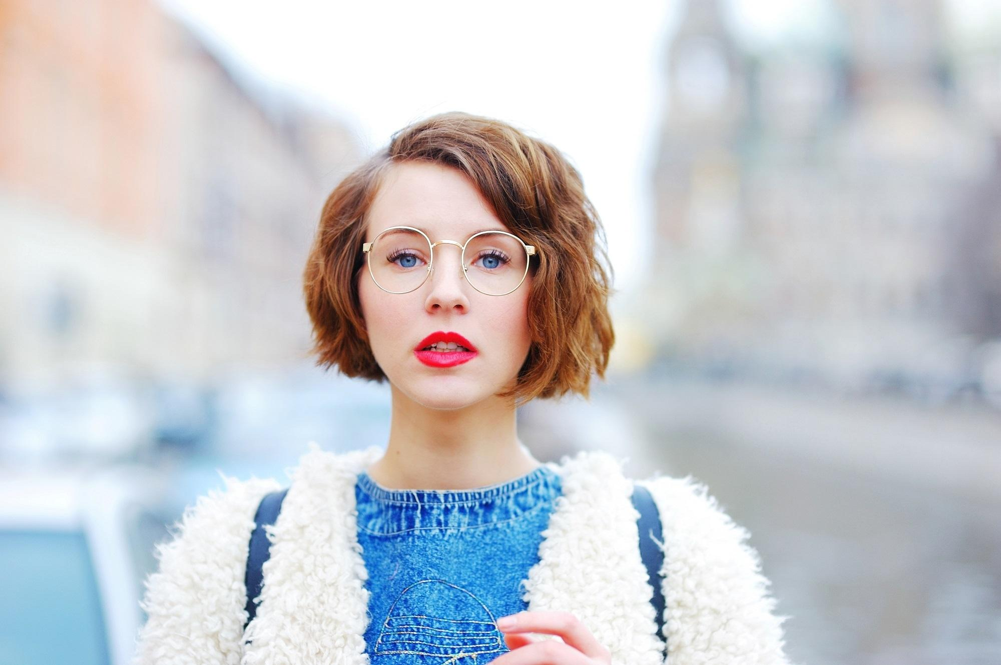 Chin length hairstyles: Closeup shot in outdoor location of a woman wearing white jacket and blue shirt with brown wavy bob and eye glasses