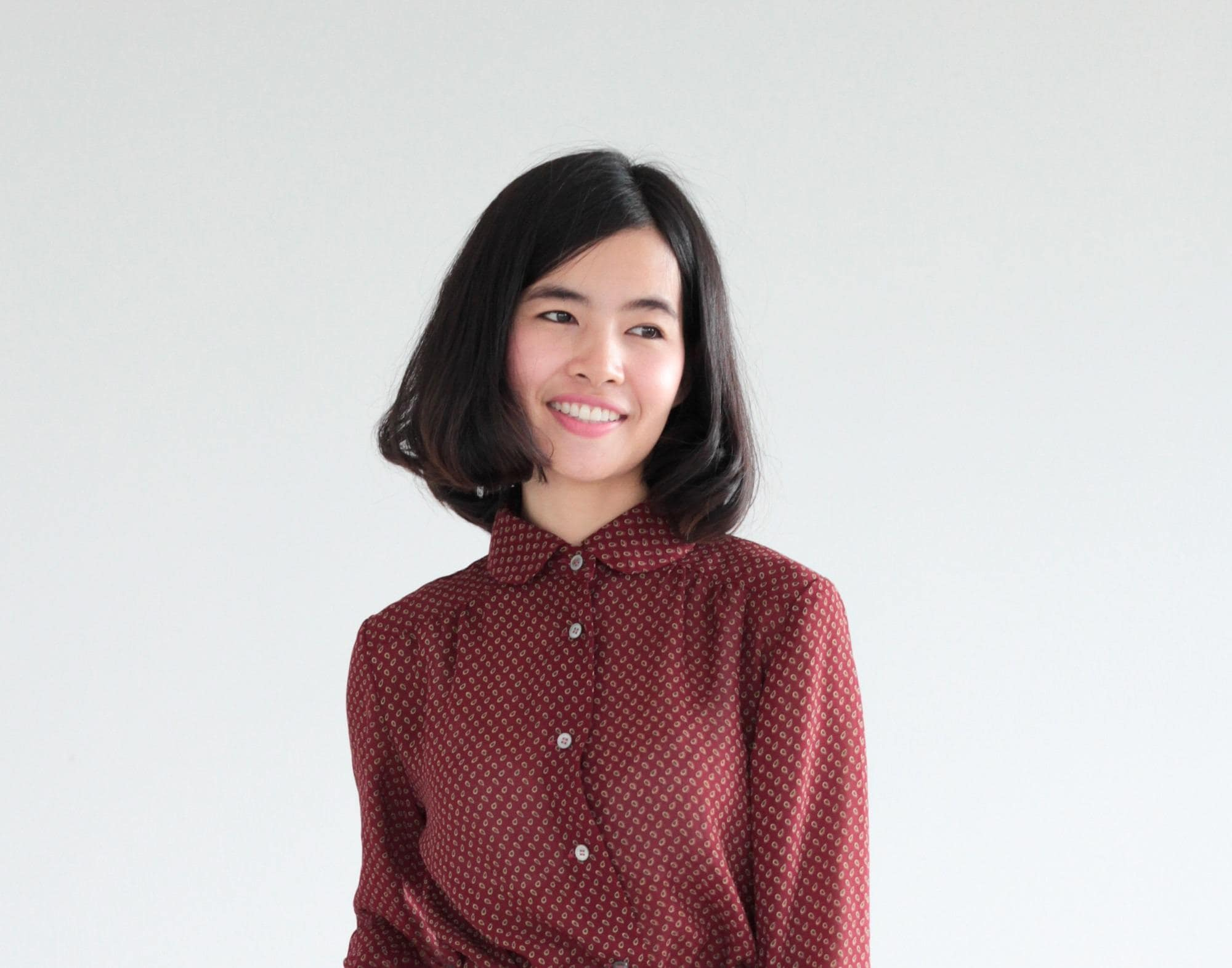 Chin length hairstyles: Asian woman wearing brown long sleeved polo with bob haircut against a white background