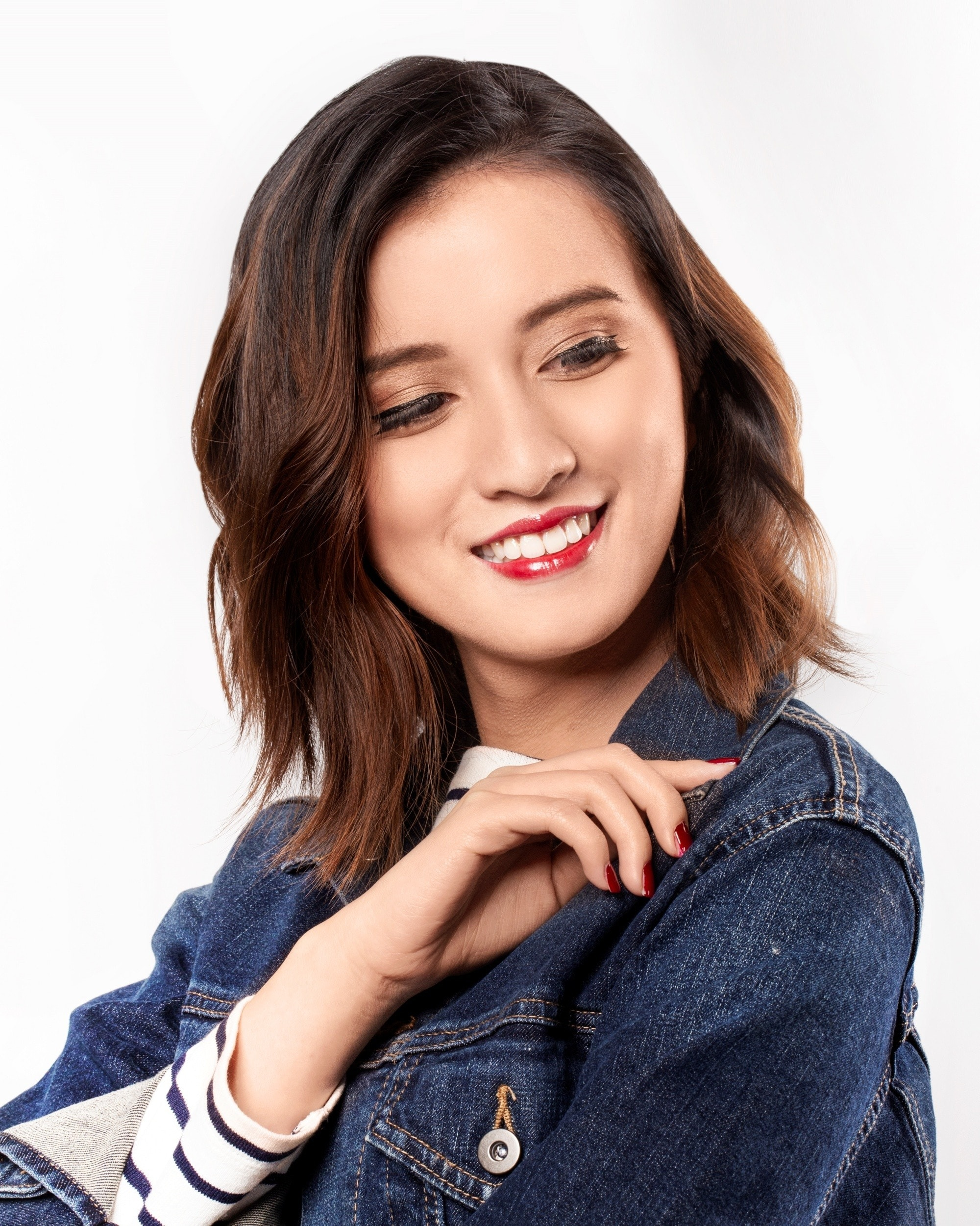 Asian woman with a tousled choppy bob hairstyle wearing a denim jacket
