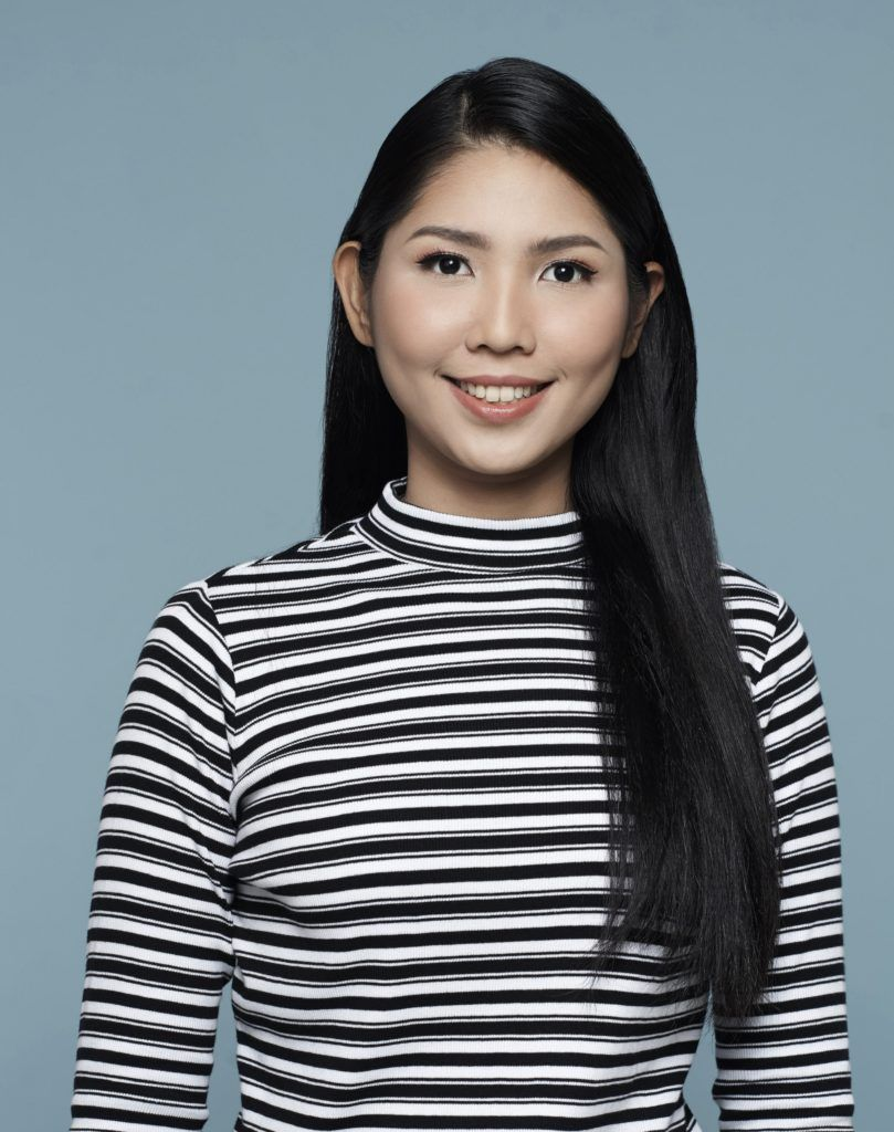 Asian woman with long black hair wearing striped shirt against blue background to start making double rope braid ponytail