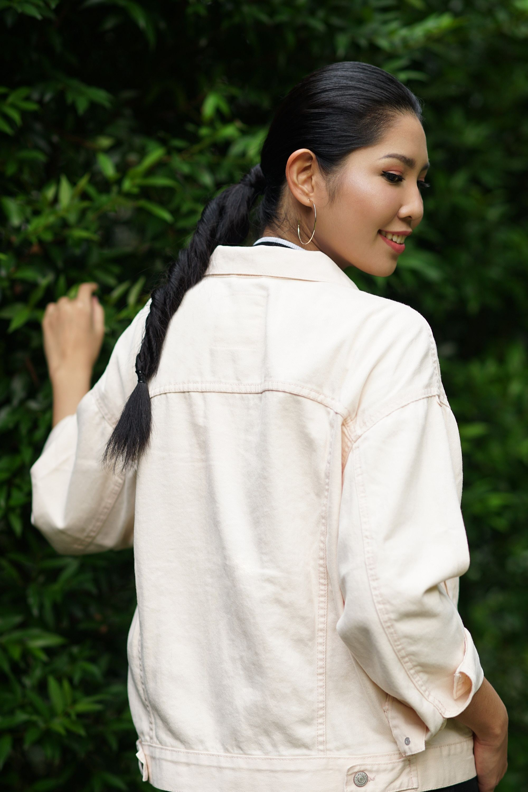 Asian woman wearing long-sleeved white polo with long black hair in double rope braid standing in front of leaves in outdoor location