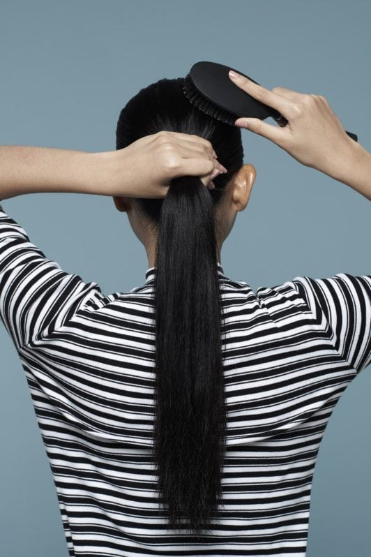 Asian woman, her back turned, with long black hair being put in a ponytail and striped shirt against a blue background for double rope braid ponytail tutorial