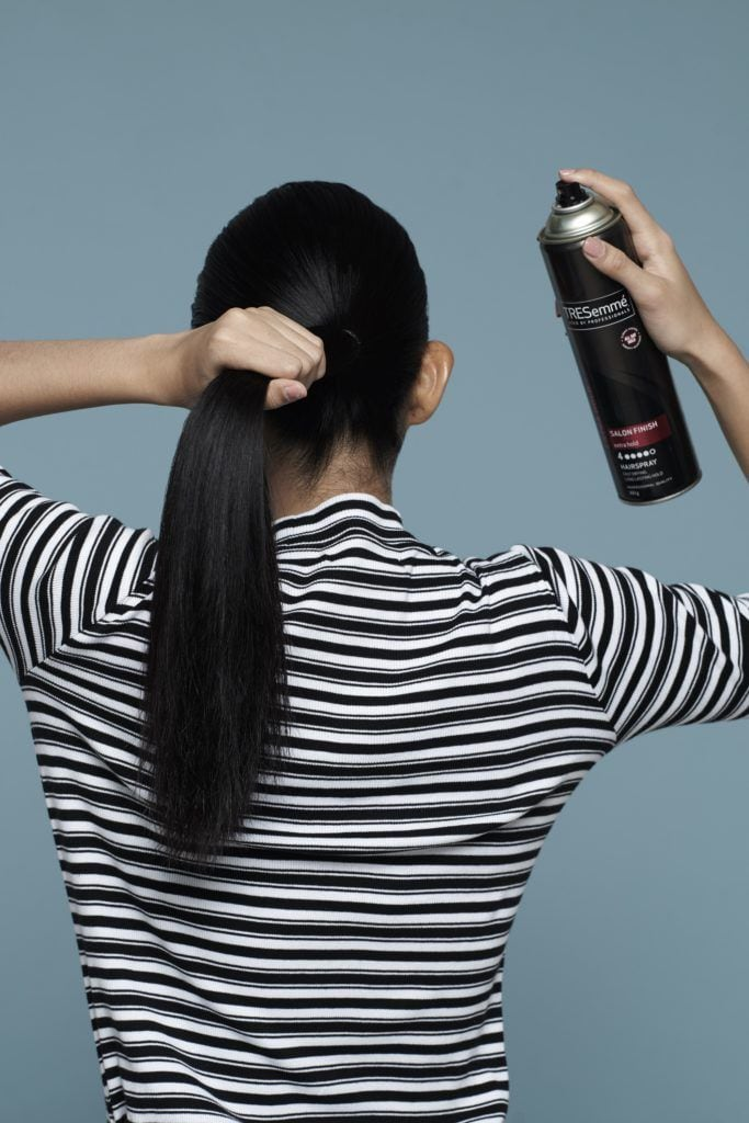 Asian woman, her back turned, with long black hair wearing a striped shirt against blue background spritzing hairspray on her hair for double rope braid tutorial