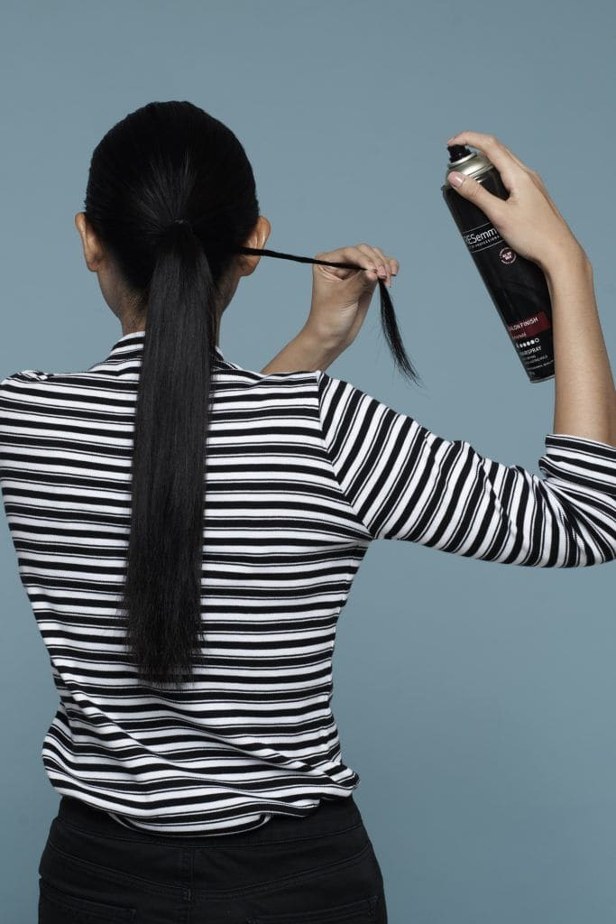 Asian woman with long black hair wearing striped shirt standing against blue background wrapping a small section of hair around the base of her ponytail for double rope braid ponytail tutorial