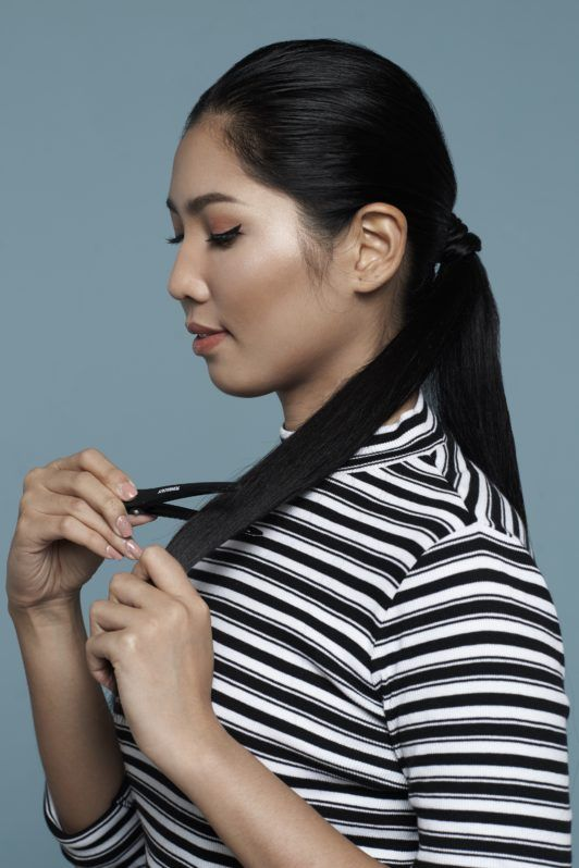 Asian woman wearing striped shirt with long black hair in ponytail dividing hair into two sections for double rope braid ponytail tutorial