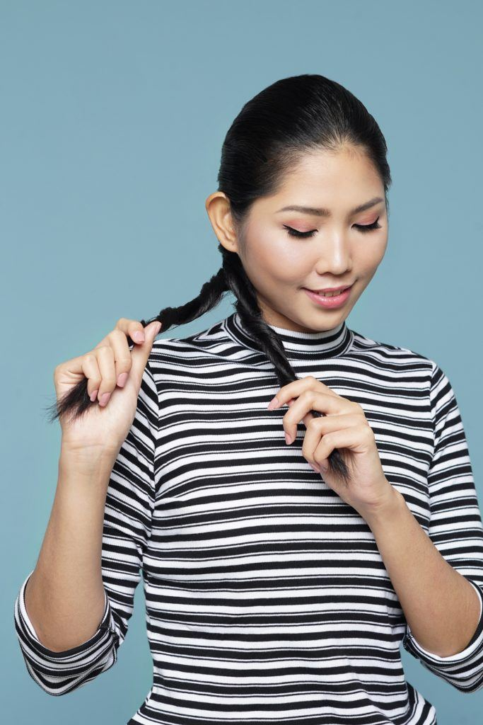 Asian woman wearing striped shirt standing against blue background putting long black hair in double rope braid ponytail