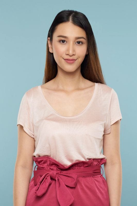 Face framing lace braid: Asian woman with long brown hair wearing light peach blouse and pink skirt standing against a blue background