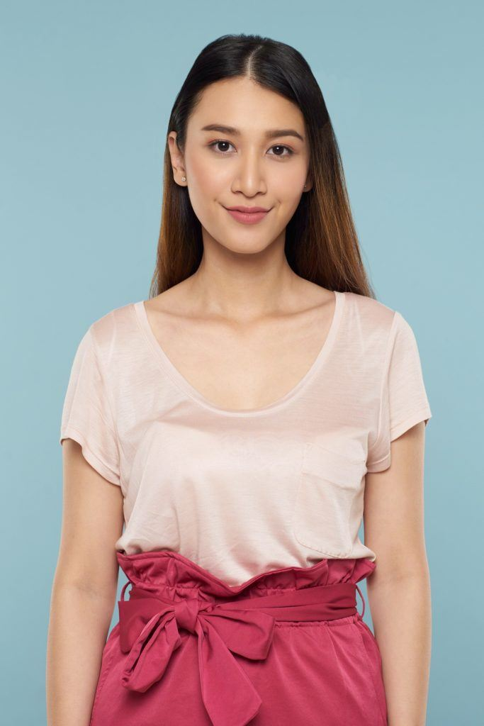 Asian woman with long brown hair wearing light peach blouse and pink skirt standing against a blue background
