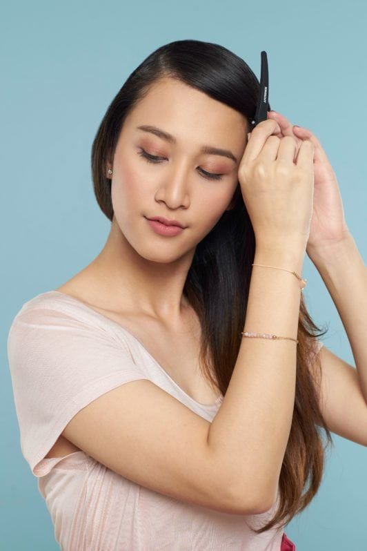Face framing lace braid: Asian woman with long brown hair wearing light peach blouse and pink skirt standing against a blue background putting a clip on her hair