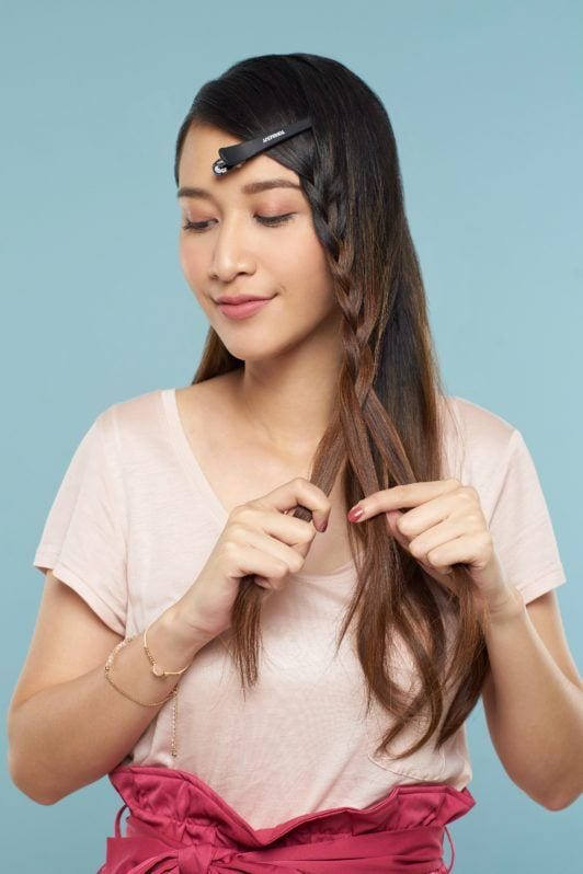Face framing lace braid: Asian woman with long brown hair wearing light peach blouse and pink skirt standing against a blue background braiding a small section of hair