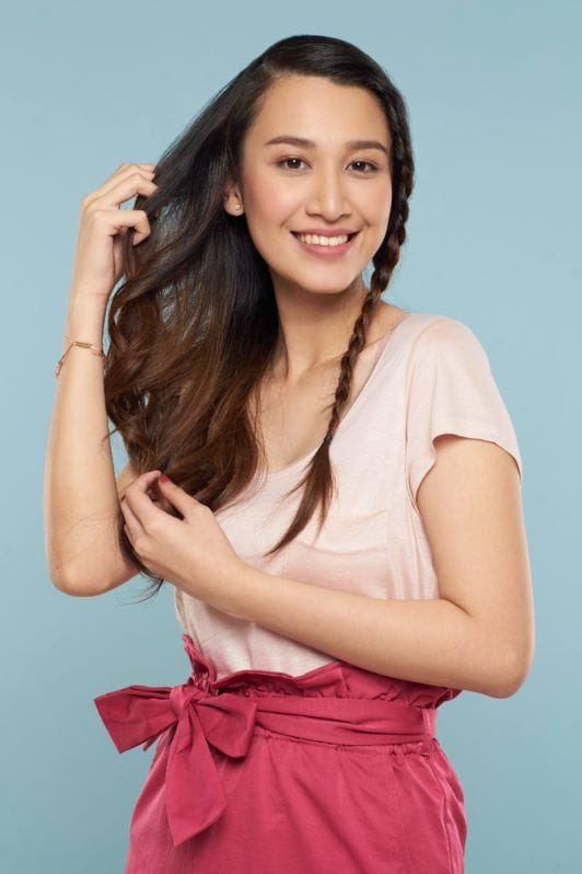 Face framing lace braid: Asian woman with long brown hair wearing light peach blouse and pink skirt standing against a blue background finger-combing her hair