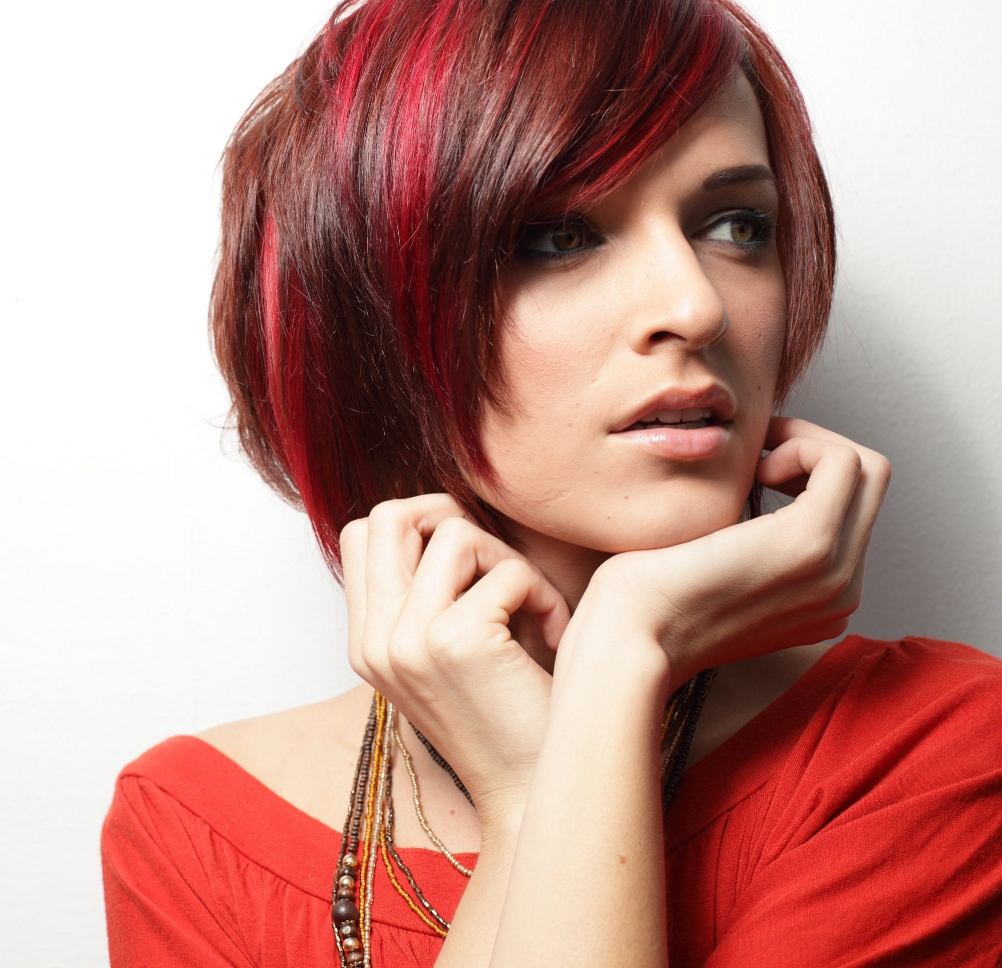 Woman wearing red orange shirt with red hair streaks on her short hair close up shot against white background