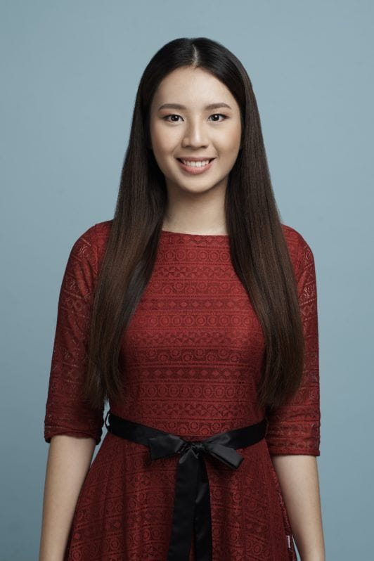 Half up criss cross: Asian woman with long black hair and red dress standing against a blue background