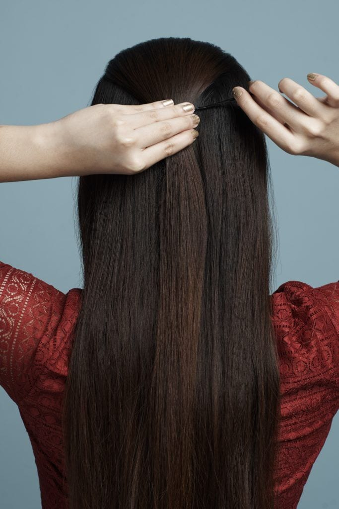 Half up criss cross: Asian woman wearing a red dress with her back turned to the camera pinning a section of her long hair near her crown and standing against a blue background