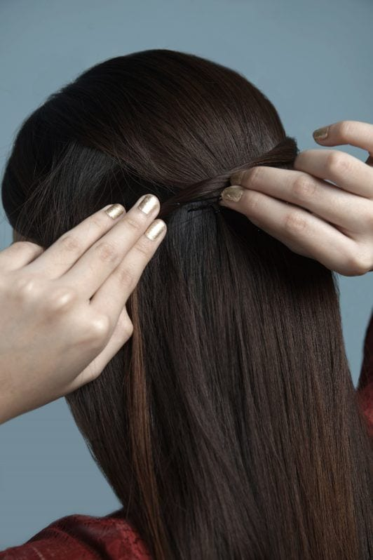 Half up criss cross: Closeup shot of hair with sections being twisted to create a half up criss cross hairstyle against a blue background