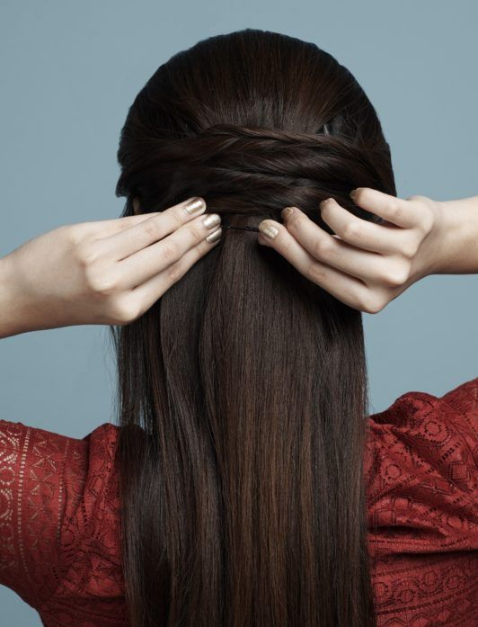 Half up criss cross: Closeup shot of the back of a woman's head with hair being styled into half up criss cross against a blue background