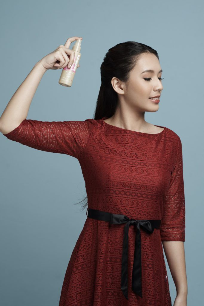 Half up criss cross: Asian woman with long black hair and wearing a red dress spritzing shine spray on her styled hair and standing against a blue background