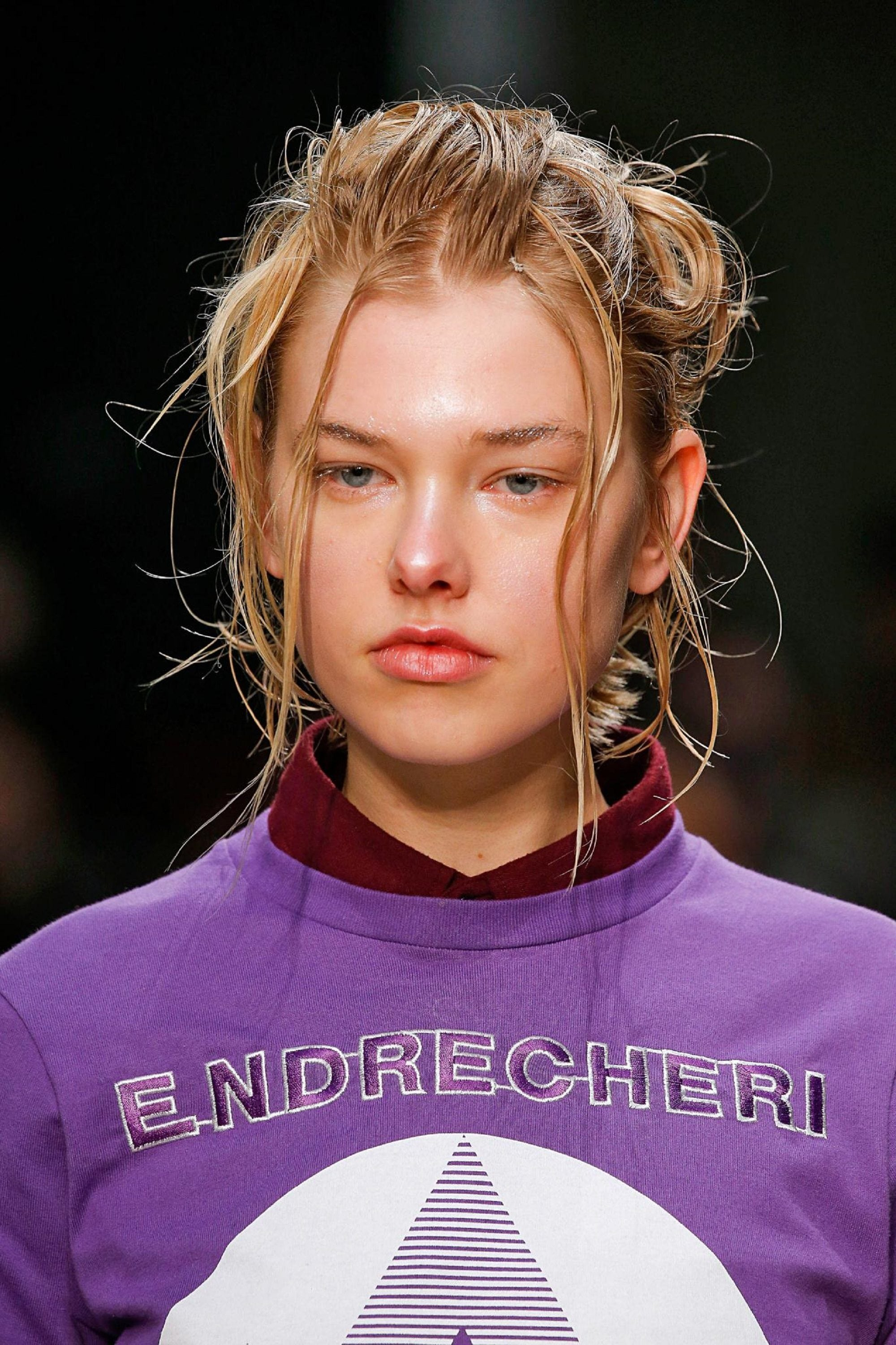 Honey hair color: Runway closeup shot of a woman with purple shirt and honey hair in a messy updo
