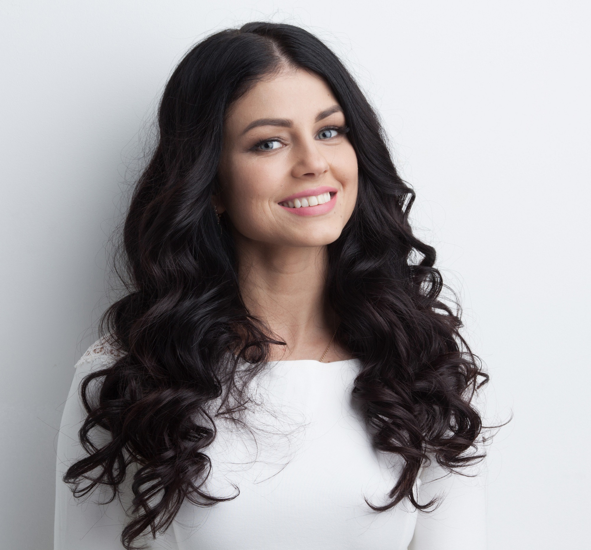 Long black hair: Closeup shot of woman with long black curly hair wearing a white blouse