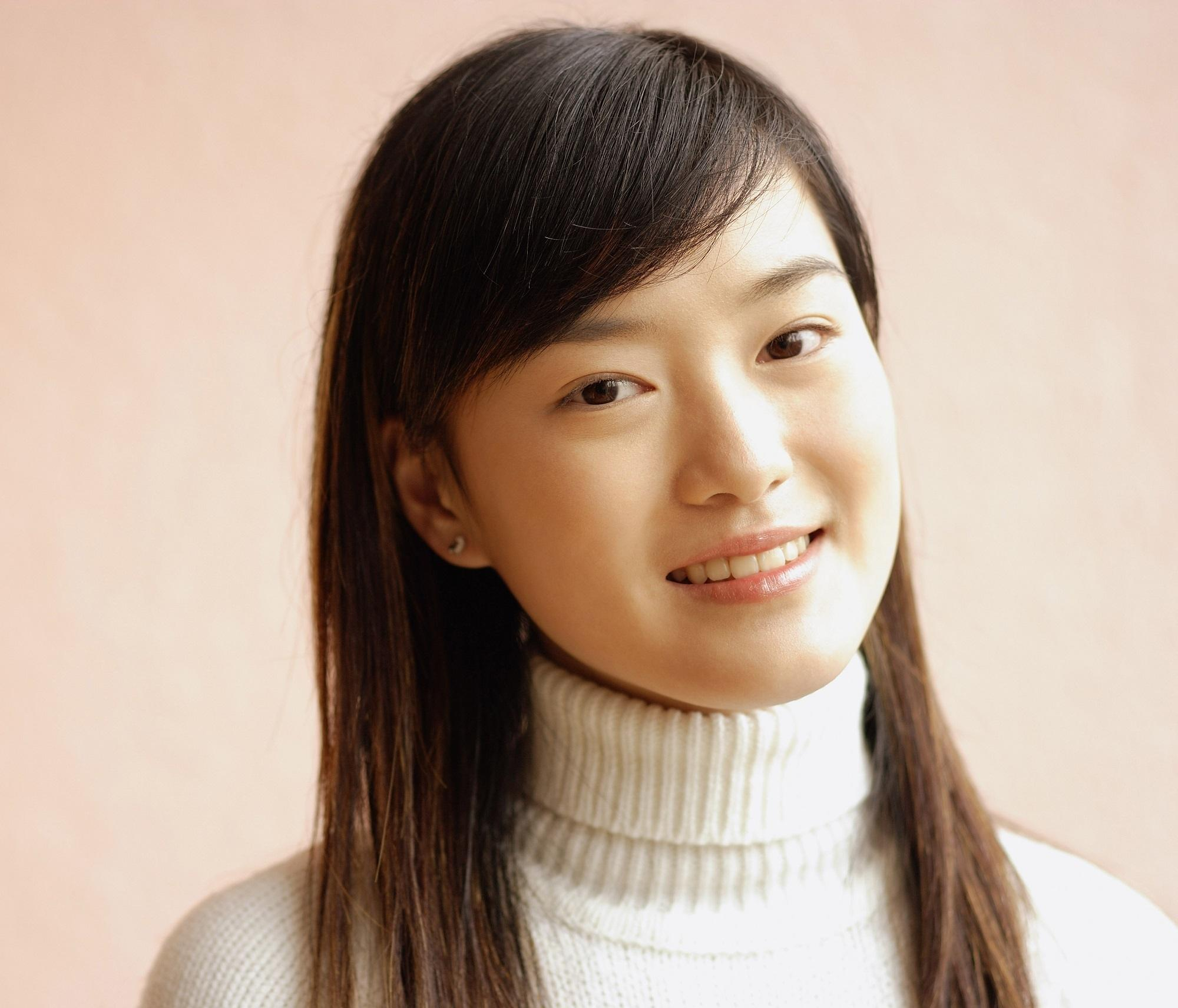 Long hair with side bangs: Closeup shot of an Asian woman with long dark brown hair wearing a white turleneck shirt against a pink background