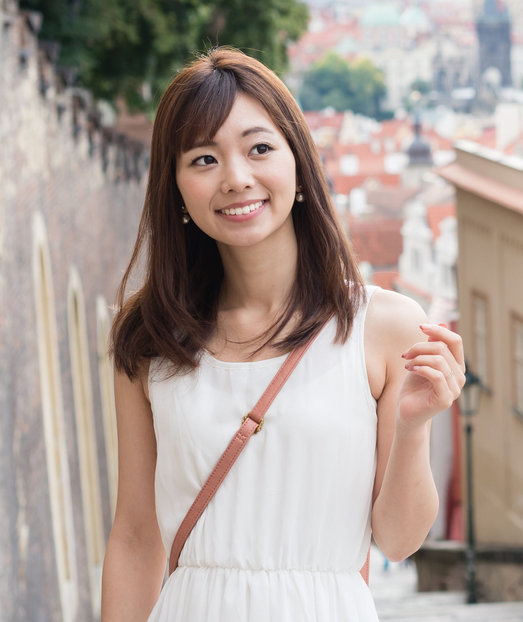 Long hair with side bangs: Asian woman with shoulder-length brown hair wearing a white sleeveless dress outdoors