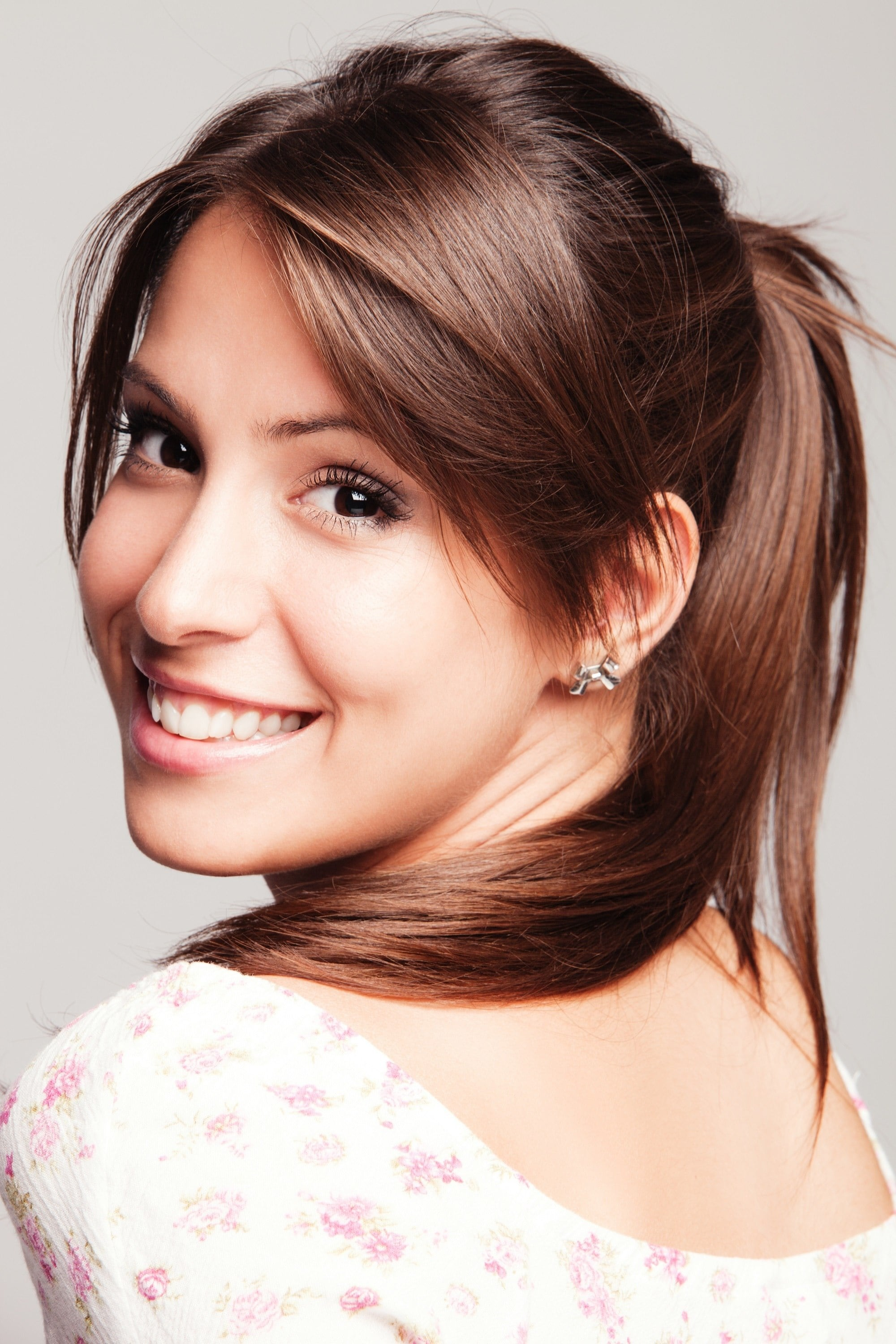 Long hair with bangs: Closeup shot of a woman with long brown hair in a high ponytail wearing a white top