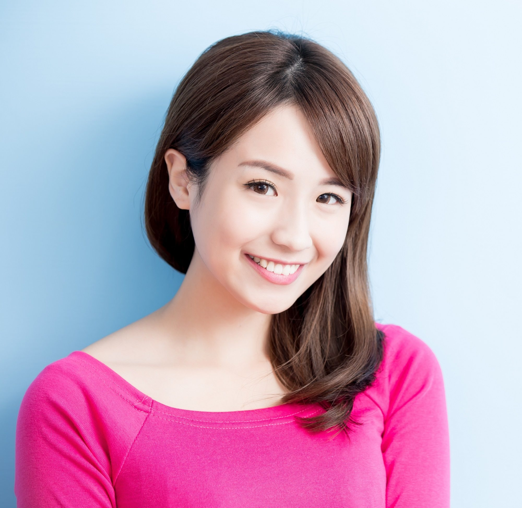Long hair with side bangs: Closeup shot of Asian woman with shoulder-length brown hair with side bangs wearing a pink top against a blue background