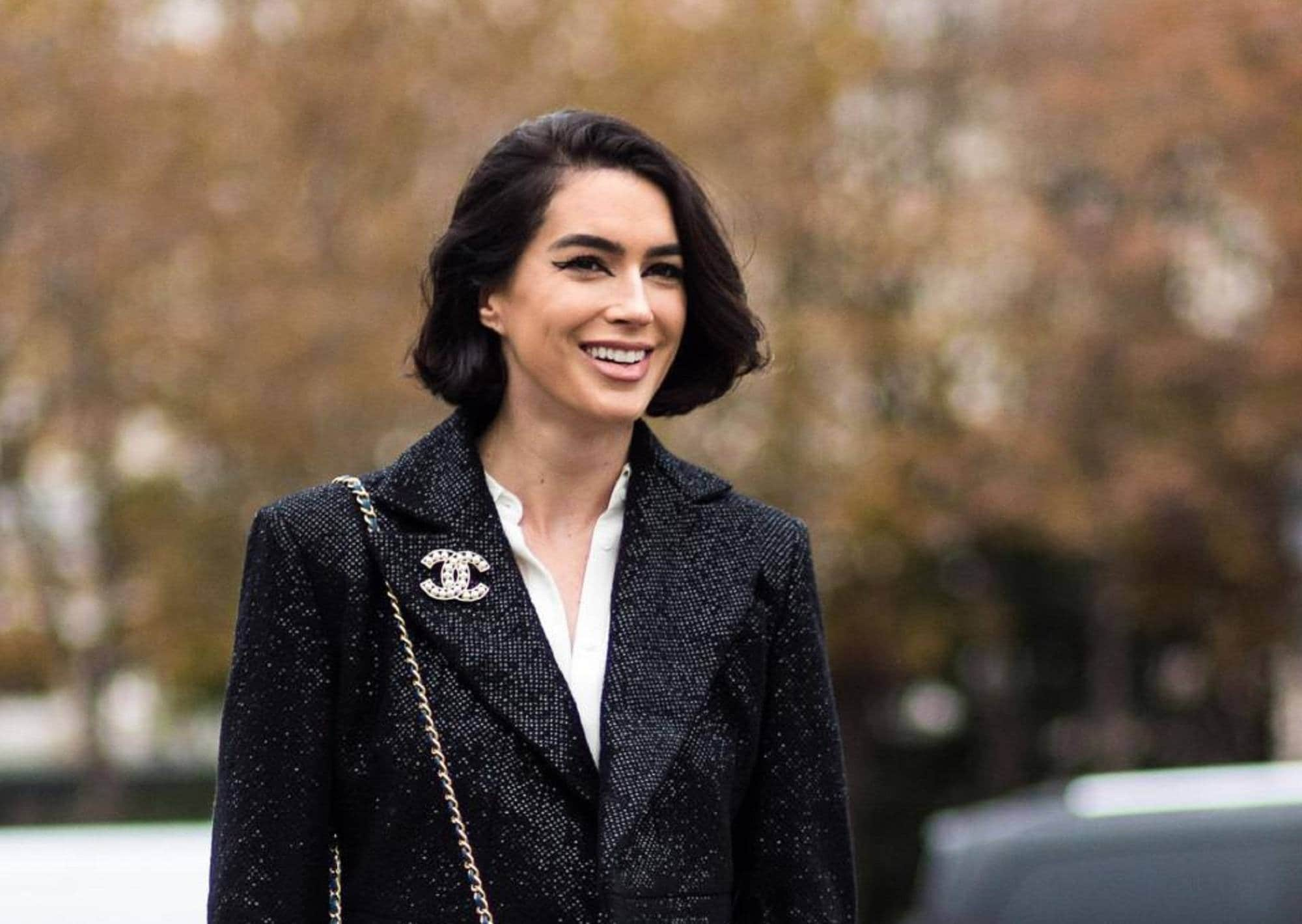 Medium bob: Closeup shot of woman wearing a black jacket with short black hair with blurred outdoor background