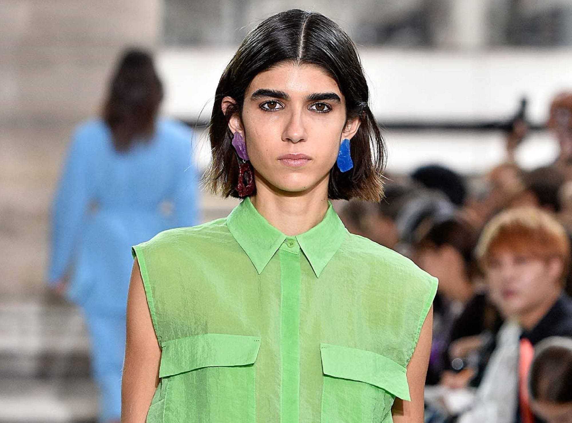 Medium bob: Closeup shot of woman wearing a green blouse with black blunt bob in a fashion show