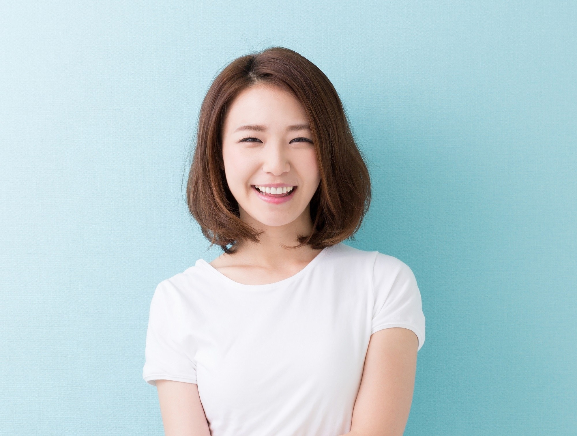 Medium bob: Asian woman wearing a white shirt with brown bob standing against a blue background