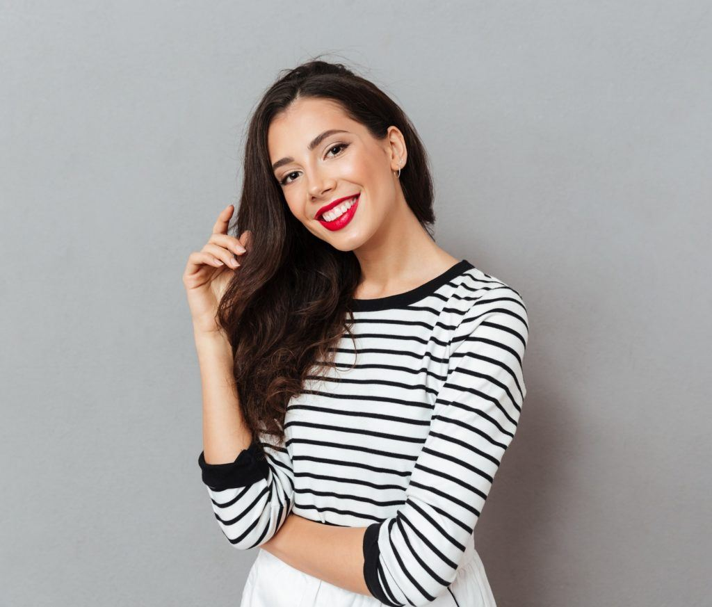 Woman standing against a gray background wearing striped shirt and has a long brown hair to represent users of serum conditioners