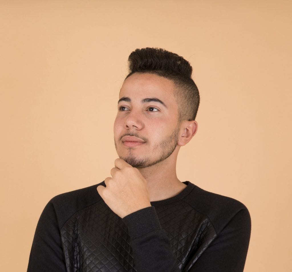 Shaves side hairstyles men: Man wearing a black long-sleeved shirt with a pompadour hairstyle standing against an orange background