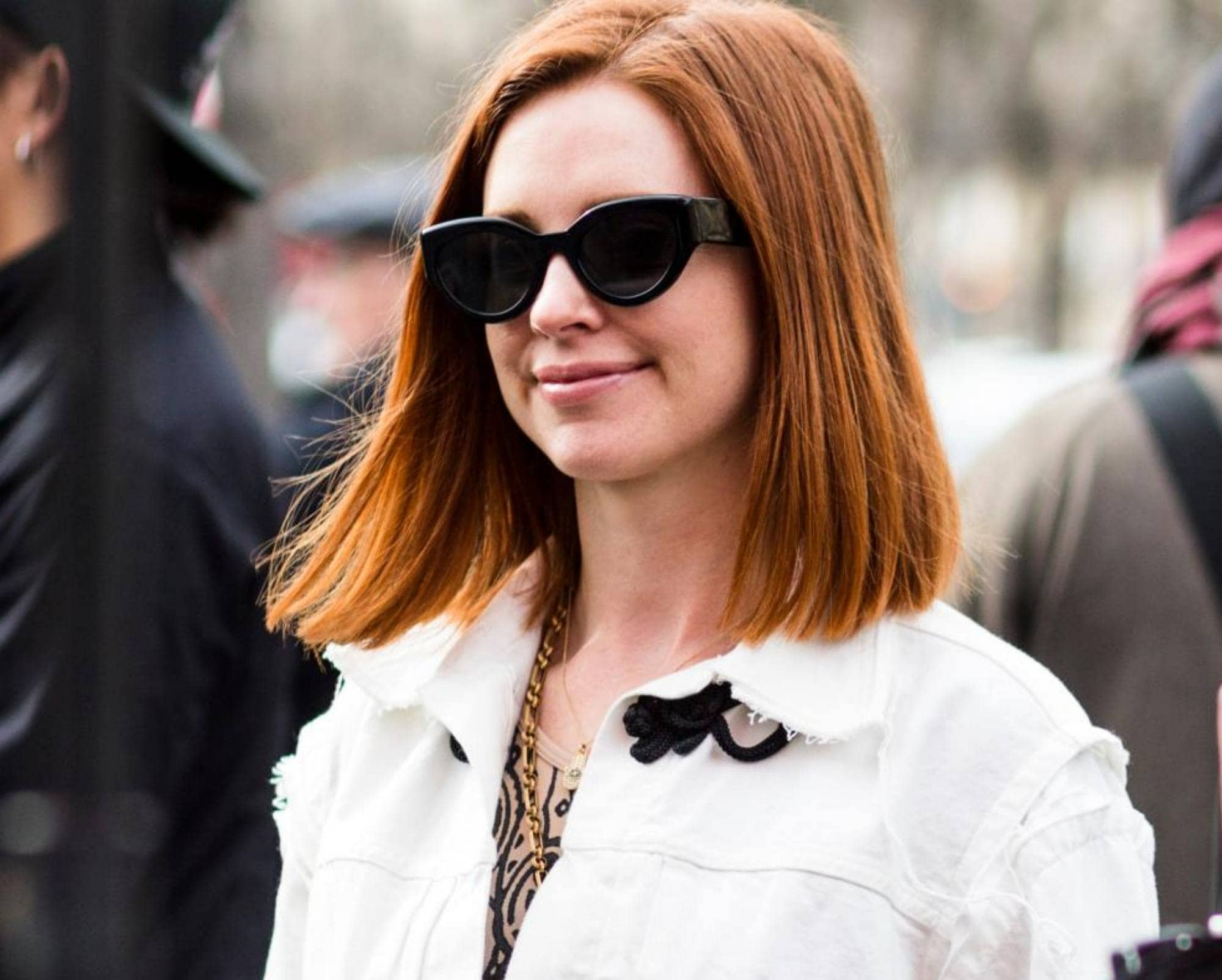 Short red hair: Closeup shot of a woman with copper lob wearing sunglasses and white jacket outdoors