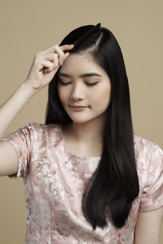 Sleek low bun with side part: Asian woman parting her hair
