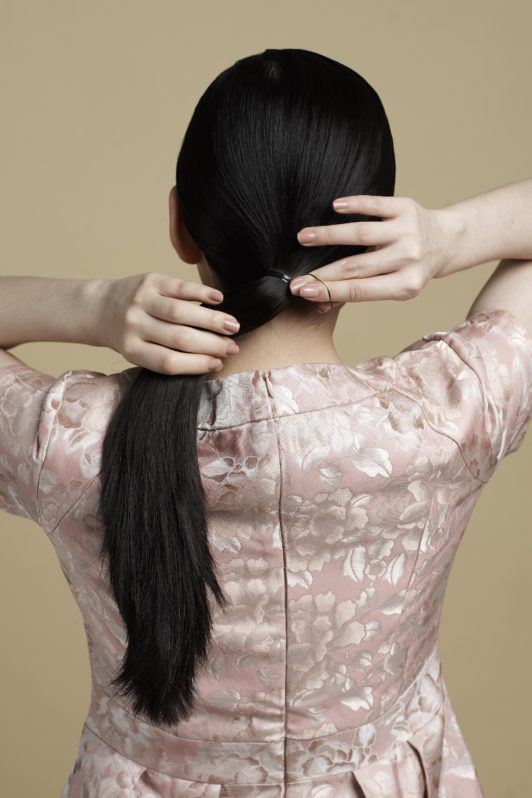 Sleek low bun with side part: Asian woman with low ponytail