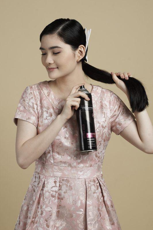 Sleek low bun with side part: Asian woman spritzing hairspray