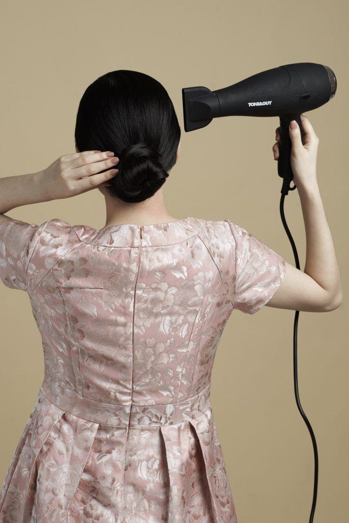 Sleek low bun with side part: Asian woman blow drying hair