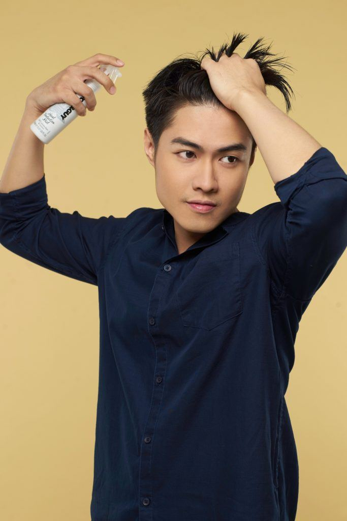 Textured and tousled medium hairstyle: Asian man spraying heat protectant on hair