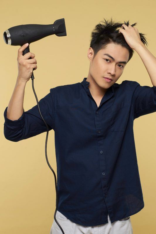 Textured and tousled medium hairstyle: Asian man blow drying his hair