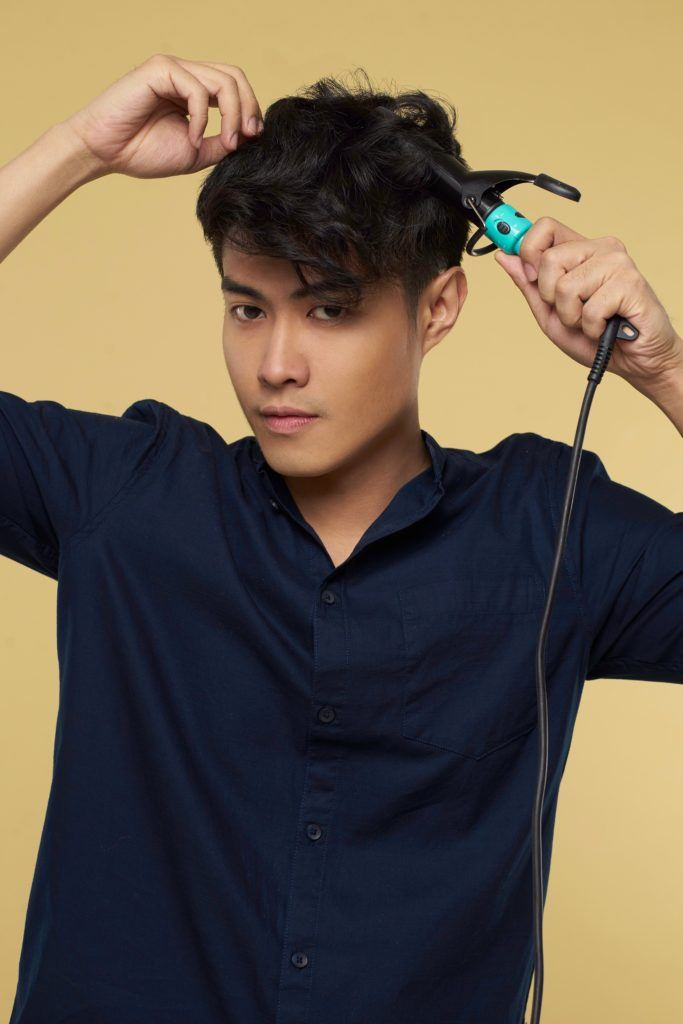 Textured and tousled medium hairstyle: Asian man curling hair