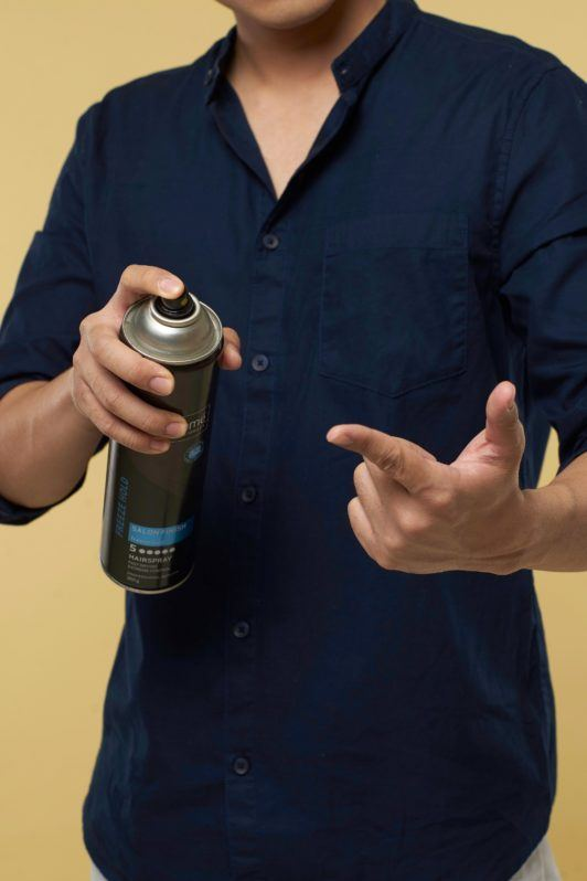 Textured and tousled medium hairstyle: Asian man spritzing hairspray on his fingers