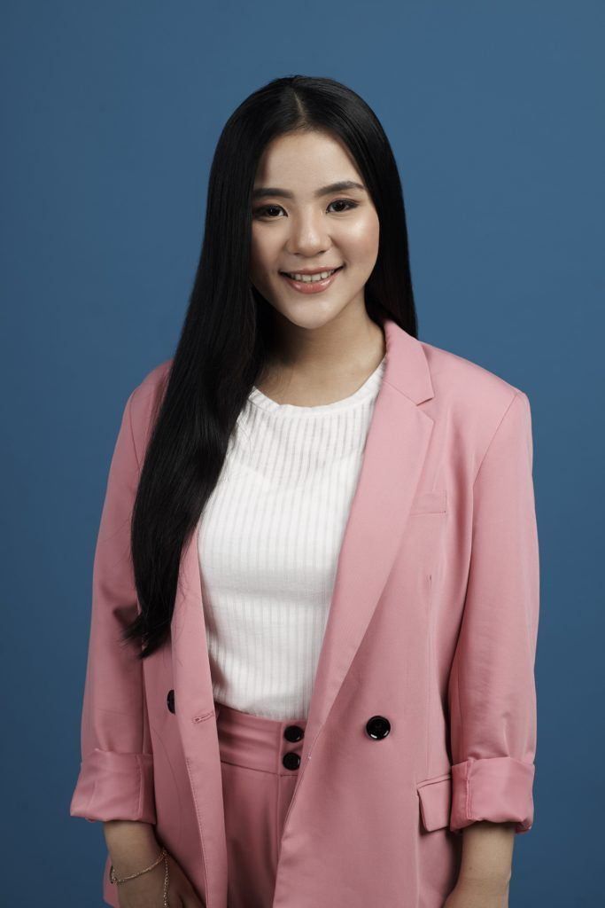 Tucked in ponytail: Asian woman wearing white blouse and pink blazer and pants with long black hair standing against a blue background
