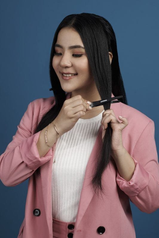 Tucked in ponytail: Asian woman wearing white blouse and pink pants and blazer with long black hair in clips standing against a blue background