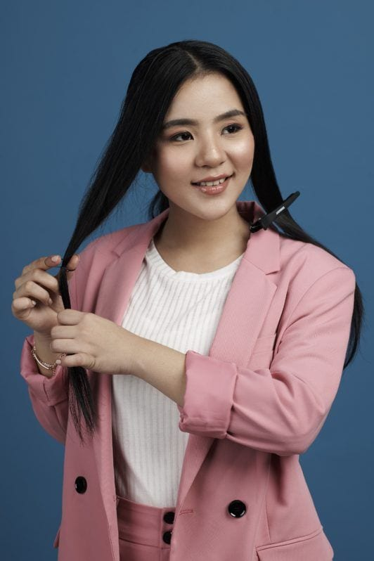 Tucked in ponytail: Asian woman wearing white blouse and pink blazer and pants tying long black hair and standing against a blue background