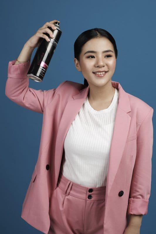 Tucked in ponytail: Asian woman wearing white blouse and pink blazer and pants spritzing hairspray on her long black hair and standing against a blue background